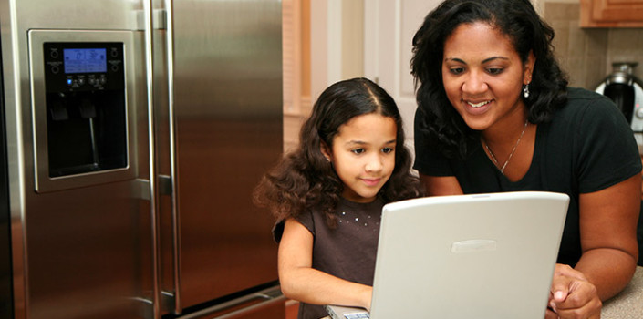 A mother and daughter on the computer in the kitchen talking about wearing deodorant